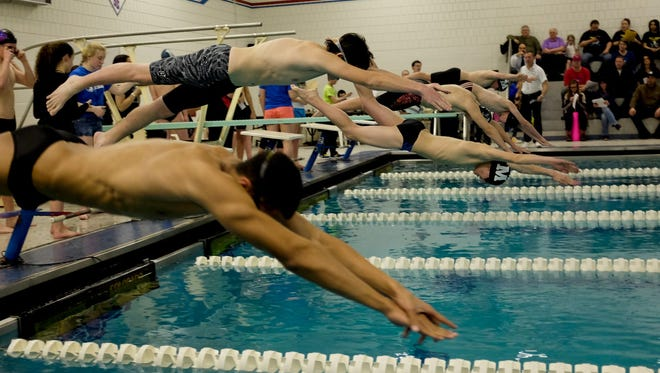 Swimmers dive off the starting block during the Blue Water Classic swim meet Thursday, Jan. 29, 2015 at St. Clair High School.