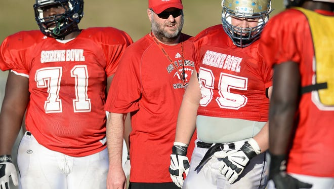 Greer's Will Young coaches the offensive line during Shrine Bowl practice at Spartanburg High School.