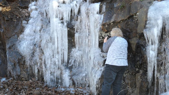 A visitor takes photos of ice on the Blue Ridge Parkway earlier this week. The entire parkway is closed until further notice.