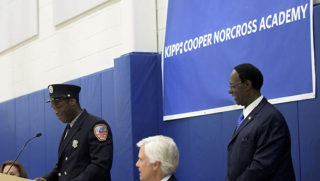 """Gilbert L. """"Whip"""" Wilson, right, smiles as Asante Wilson speaks on behalf of his father Carlton E. """"Muscles"""" Wilson, who was recently hospitalized, at a dedication ceremony Wednesday in Camden. The KIPP Cooper Norcross Academy gym was officially dedicated to brothers Gilbert and Carlton."""