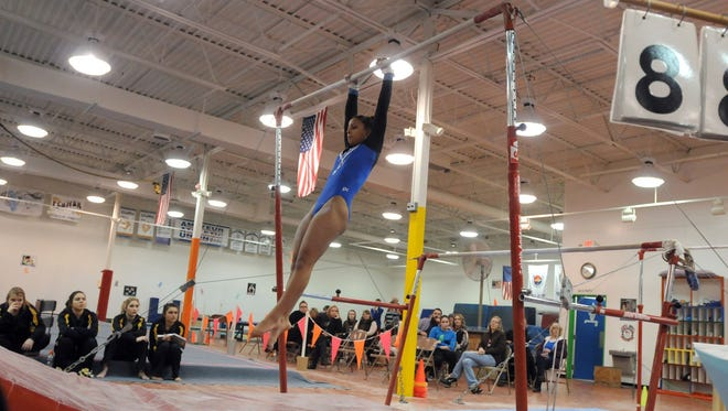 Port Hurons' Bri Smith swings around on the uneven bars Monday, Feb. 22, during a gymnastics meet against Fraser at Kaleidoscope Gymnastics.