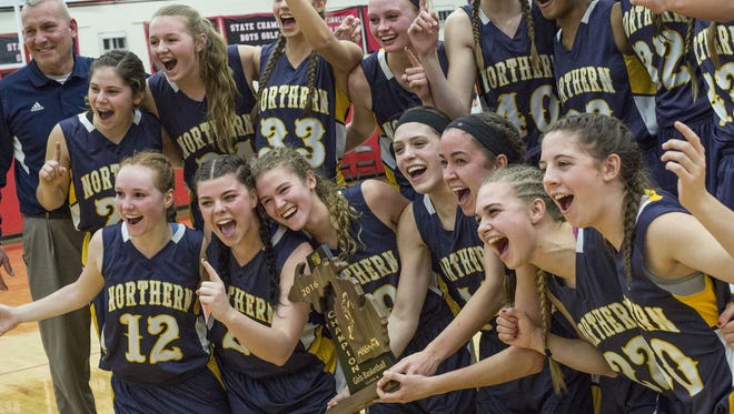 Port Huron Northern players pose with the trophy after beating Fenton 40-38 in a regional final basketball game Thursday, March 10, 2016 at Grand Blanc High School.