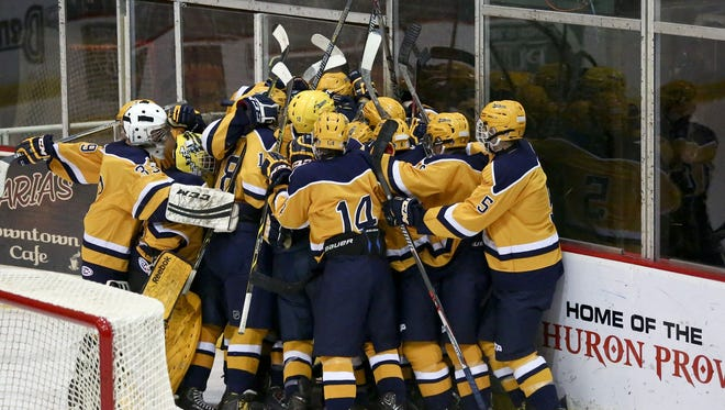 Port Huron Northern players celebrate beating Anchor Bay during the Larry Manz Holiday Hockey Tournament Saturday, November 28, 2015 at McMorran Arena. Northern beat Anchor Bay 6-5 in overtime.