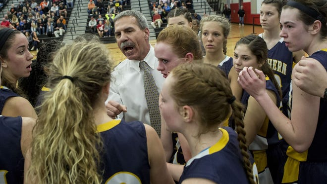 Port Huron Northern coach Mark Dickinson talks with players in a huddle during a regional final basketball game Thursday, March 10, 2016 at Grand Blanc High School.
