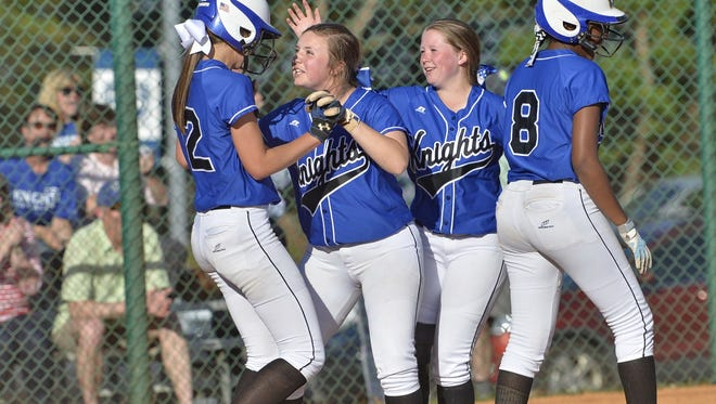 St. Joseph's Sydney Richardson, left, celebrates with teammates Monday after hitting an inside-the-park grand slam in the third inning of the Knights' 22-0 win over visiting Christ Church.
