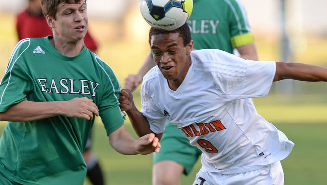 Mauldin's Austin Tuggle (9) heads the ball past Easley's Jack Weyman (3) during the Mavericks' 5-4 win in the first round of the Class AAAA boys soccer playoffs Tuesday night at Freeman Field.