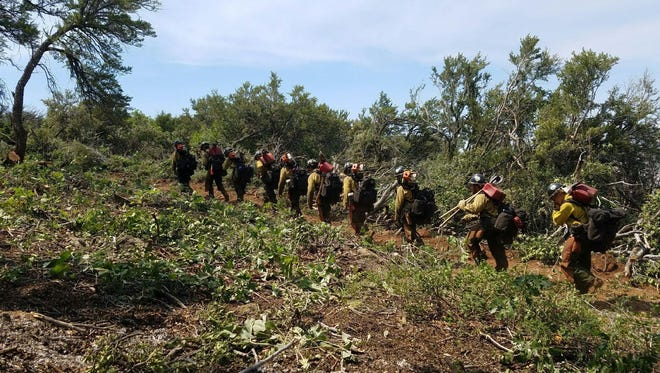 A Hotshot crew of firefighters works to carve out defensible fire lines around the Saddle Fire, which has grown to 1,540 acres on the mountainsides above Pine Valley.