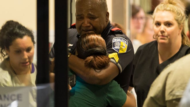 A Dallas Area Rapid Transit police officer receives comfort at the Baylor University Hospital emergency room entrance Thursday in Dallas.