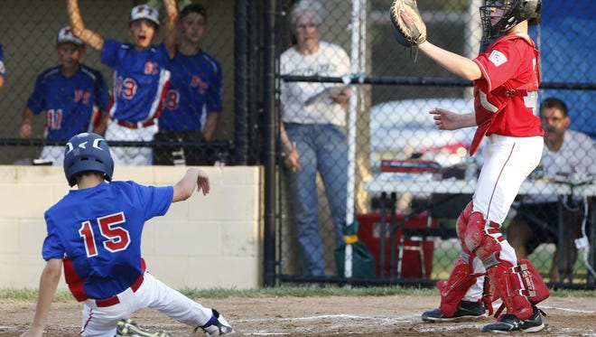 Colin Reilly (left) of Freehold Township scores against Holbrook during their Little League Section 3 playoff game Sunday, July 17, 2016, at Michael J. Tighe Park in Freehold Township.