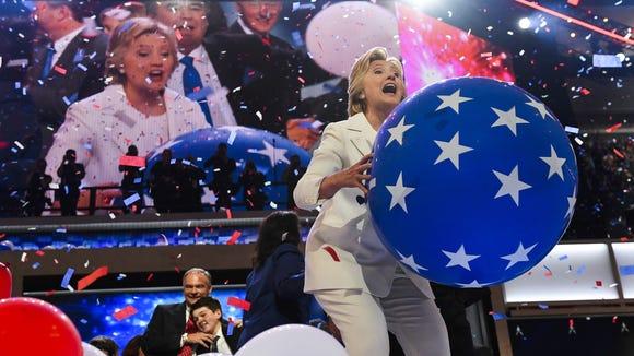Hillary Clinton throws a balloon into the crowd at