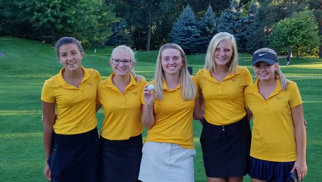 Gabbi Reed (center) stands with her Hartland teammates after sinking the first hole-in-one in school history on Tuesday at Oak Pointe Country Club in Brighton.