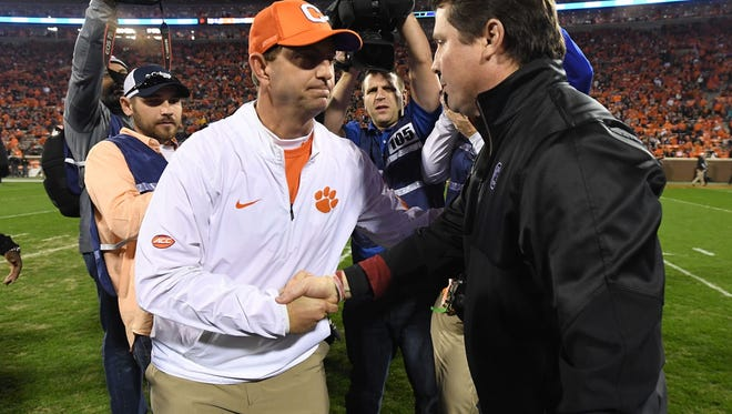 Clemson coach Dabo Swinney, left, shakes hands with South Carolina coach Will Muschamp prior to Saturday night's game at Memorial Stadium.