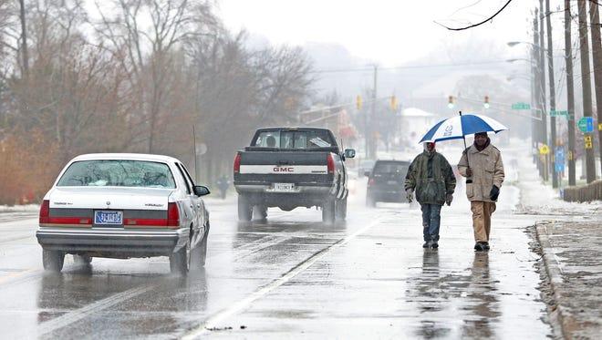 Pedestrians walk north on a rain-soaked sidewalk up Martin Luther King Jr. Dr., Saturday, December 17, 2016.
