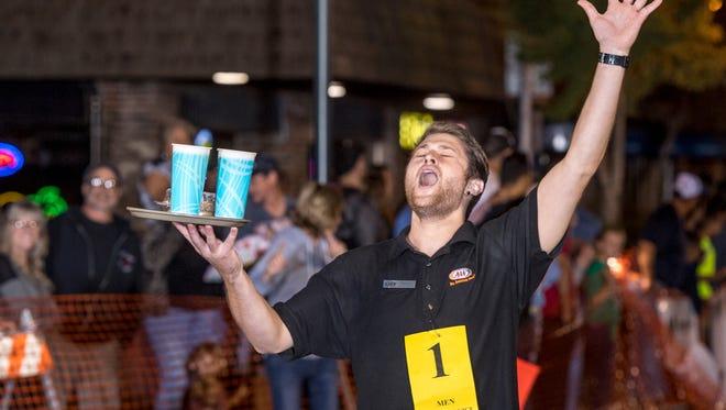 A&W's Brandon Kennard wins the men's fast service final in the Annual Visalia Waiters Race in Downtown Visalia on Thursday, September 21, 2017.