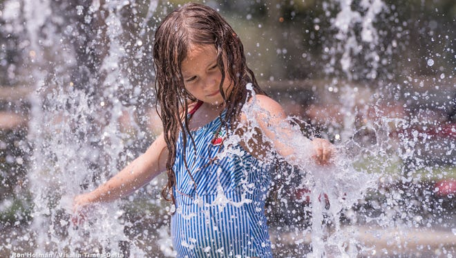 Isabel Wallace, 6, plays in the fountains of the splash pad at Riverway Sports Park on Thursday, July 26, 2018.