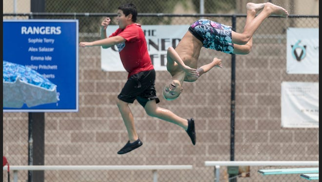 Caleb Vilhauer, 12, left, and Leo Barrios, 11, dive during public swim at Redwood Community Pool on Friday, July 27, 2018.
