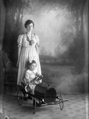A young woman and child pose in Joseph Bishop's photography studio. The toy car appears in several of Bishop's portraits.