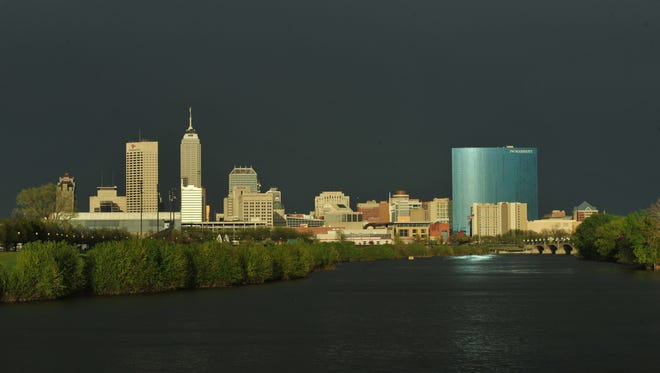 The low sun reflects off the downtown Indianapolis skyline looking down the White River from New York Street, after a storm blew over and the sun emerged from behind the clouds, Tuesday April 29, 2014.  One America tower, Chase Tower, JW Marriott hotel.