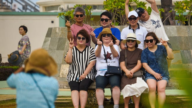 A group of tourists visiting the island from Korea pose for a group photo during a stop at Puntan Dos Amantes, or Two Lovers Point, on Saturday, March 31, 2018.