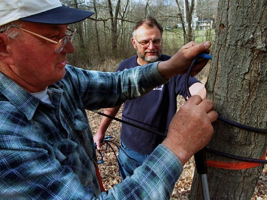 In this 2000 photo, Edmund Motz (left) and his cousin Matt Motz fix a tap in a maple tree on their family maple syrup farm in Anderson Township. Both men are now deceased, but Matt Motz's four sons continue the tradition.