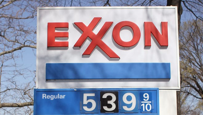 Exxon-Mobil reported its second-quarter 2014 earnings on July 30, 2014. In this photo, a sign shows gas prices over five dollars a gallon for all three grades at a EXXON service station on March 13, 2012 in Washington, D.C.