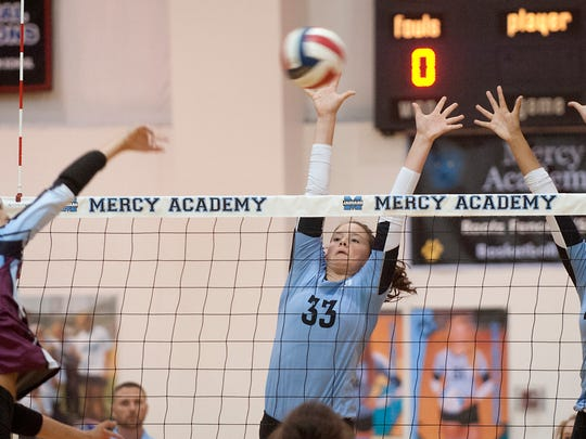 Assumption outside hitter Maryann O'Toole powers the ball toward Mercy opposite hitter Emma Schurfranz, center, and Mercy middle blocker Neci Harris, right. Assumption beat Mercy 26-24, 25-15 and 25-17 to retain their #1 state standings against #2 Mercy.