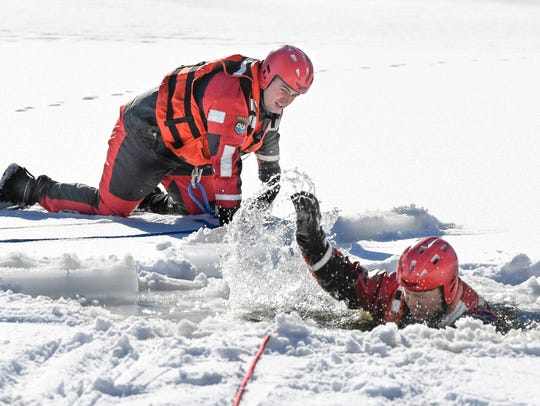 Henderson city firefighter Cory Agnew crawls around to get into position to rescue assistant chief Chad Moore during an ice rescue training session at Audubon State Park Thursday.