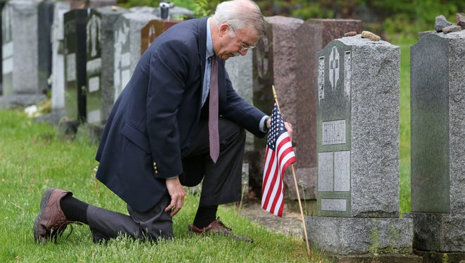 Robert Abate of Yonkers kneels as he places a U.S. flag at the grave of WWII Navy frogman veteran Ray Hyman at the Gates of Heaven cemetery in Hawthorne May 19. Abate, himself a Navy veteran, has interviewed more than 100 combat veterans of WWII and had a special affinity for Hyman, who was a member of the Navy's Underwater Demolition Team in the Pacific.