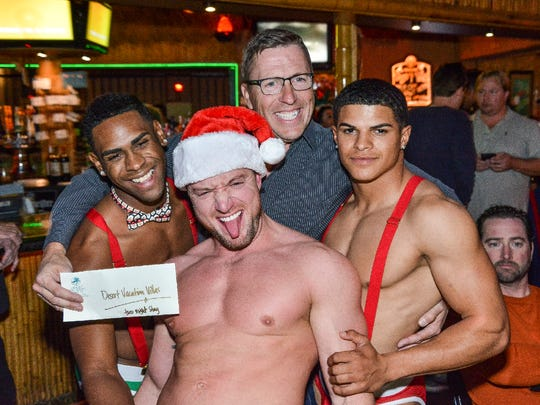 Rene Bernard (center) and Santa's elves during the Toys for Tots drive at Toucans Tiki Lounge.