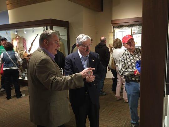 Joe Zuckschwerdt, president of the John Wayne Birthplace Museum, shows Iowa Gov. Terry Branstad memorabilia from Wayne's movies.