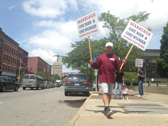 Tony Valentini, of Penfield, carries signs at a traditional marriage rally in Rochester Saturday.