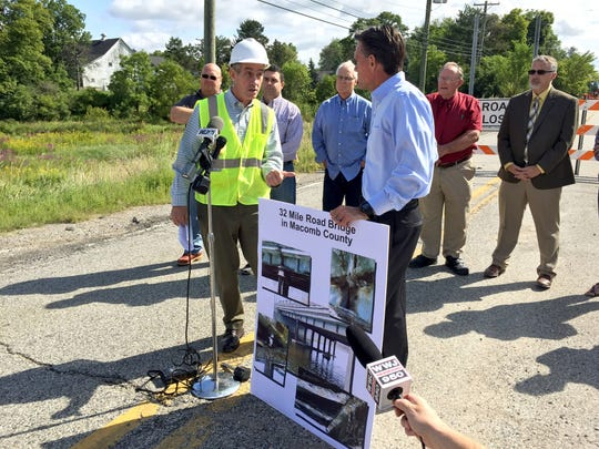 Macomb County Roads Department Director Bob Hoepfner, left, talks with county Executive Mark Hackel about the 32 Mile Road bridge and related road funding matters Aug. 25, 2015 as local leaders listen. The 32 Mile bridge, which has been closed for months, is on the Armada-Ray townships border.
