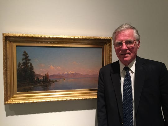 """Art historian Alfred Harrison stands in the gallery next to one of his favorite paintings from the Oakland Museum of California collection, """"View of Lake Tahoe"""" by John Ross Key. The painting is on view through January 10 at the Nevada Museum of Art as part of """"Tahoe: A Visual History."""""""