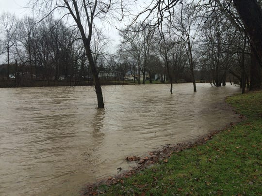The Little Miami River swells Sunday afternoon in the village of Morrow in Warren County.