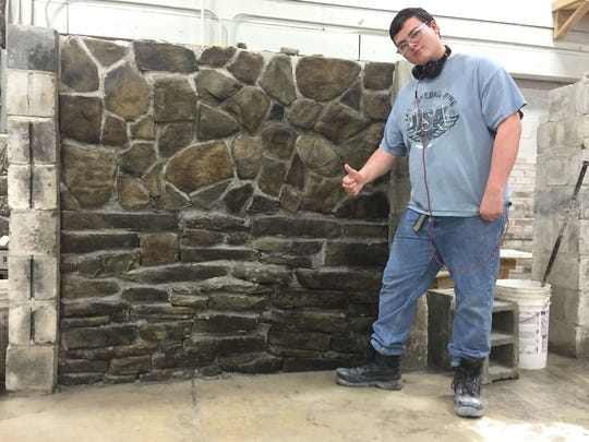 Michael, a student at Broome-Tioga BOCES, poses next to a all he built as Bob Squier takes his photo.