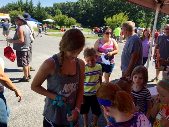 Brooke Edwards lets people at a booth, giving away free water and popsicles,  to pet her dog Ace.