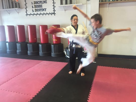 Tory Lombardo holds a jump pad for a student during