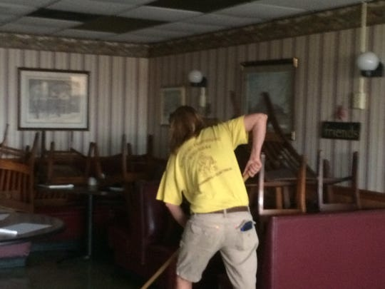Tina Williams with American Home Spec works to clean up after an early morning fire at Eastgate Diner.