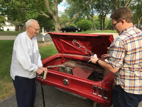 Harry Donovan, 95, and his grandson, Harry Donovan IV, examine parts in the trunk of the World War II veteran's 1967 Mustang. Several area car enthusiasts and veterans' groups are working to restore Donovan's car after he was ripped off by another man he paid thousands to do the work.