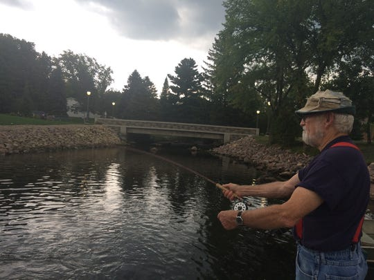 Art Robson, an Amherst resident, fishes near the newly renovated Amherst millpond dam.