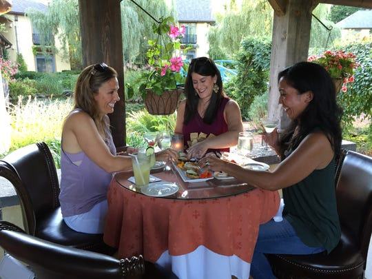 Adena Miller, center, and friends Anne Miller, left, and Edie Catlin enjoy appetizers and drinks at Mirbeau Inn and Spa in Skaneateles.