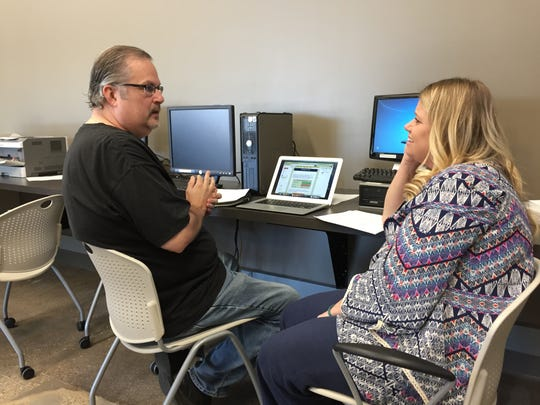 Health-insurance navigator Nicole Kock of Visiting Nurse Services, helps consumer Scott Lewellen of Des Moines understand his options under the Affordable Care Act during an insurance enrollment fair in Johnston.