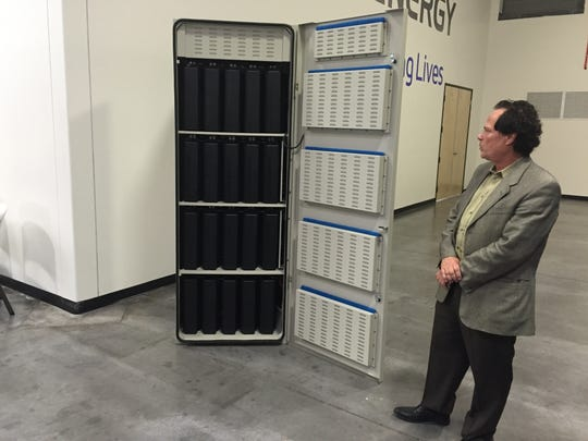 Tom Harris, director of business development for Sky Renewable Energy in Phoenix, admires the Fluidic Energy battery he bought for his home.