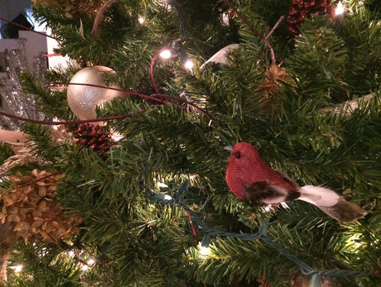 A cardinal perches on a Christmas tree decorated by