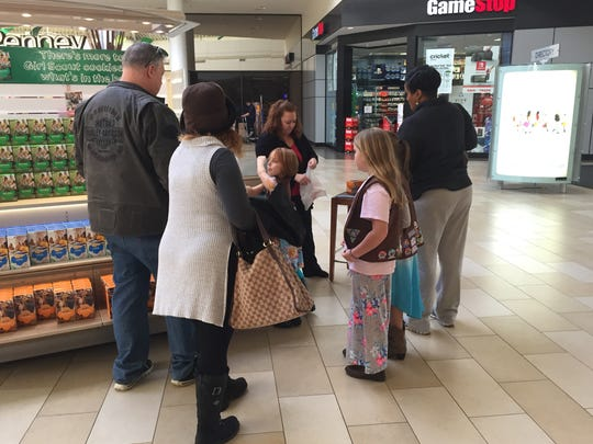 Prospective buyers fish for the $4 or $5 necessary to buy their favorite Girl Scout Cookies at the Christiana Mall.