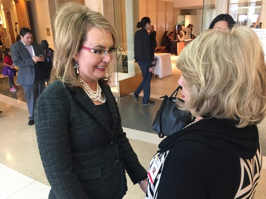 Former U.S. Congresswoman and mass shooting survivor Gabrielle Giffords, left, greets an admirer at the Statehouse in Santa Fe, N.M., on Wednesday, Feb. 22, 2017. Giffords and her national gun-safety advocacy group Americans for Responsible Solutions are trying to build support for bills that would expand background checks on private firearms sales in New Mexico and remove guns from domestic violence situations where a restraining order has bee issued.