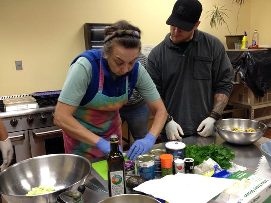 Chef Cynthia Kroon shows Americorp member/volunteer Justin Reid an easy way to prepare tomato slices for the avocado-egg salad.