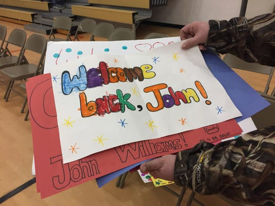 Caren Sessions hold signs made for her son, Johnathan