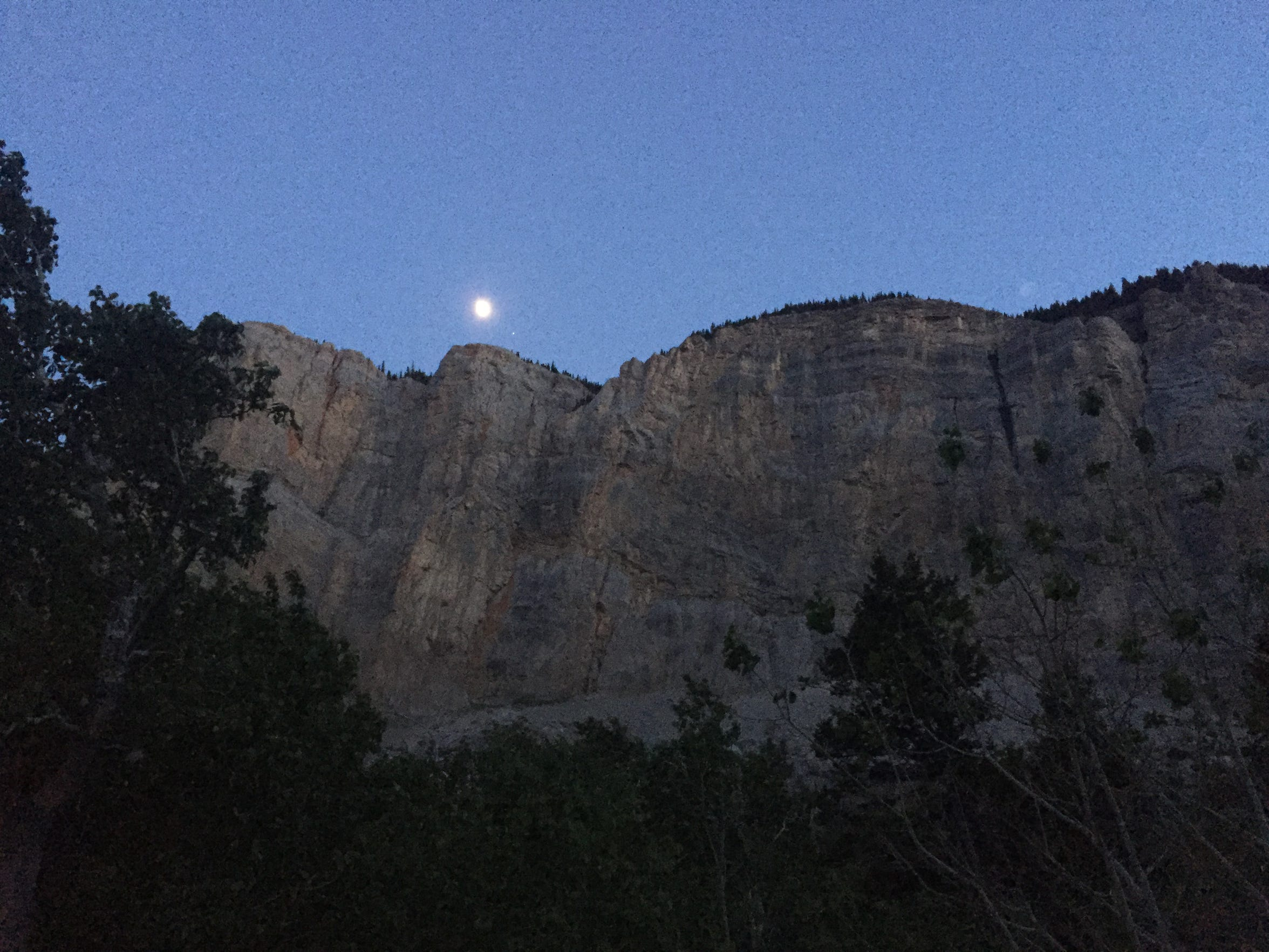 A full moon glows atop the walls of the Blackleaf Canyon. Primitive camping spots are scattered around the canyon trailhead.