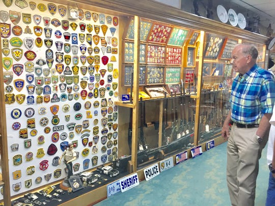 Tallahassee Auto Museum owner DeVoe Moore with the collection of law enforcement badges, patches, batons and model cars recently donated to his museum by H.A. Freels.